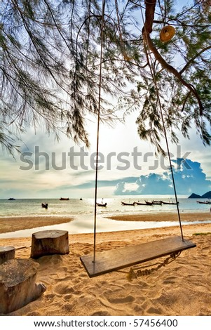 Swing on a tropical beach against the setting sun - stock photo