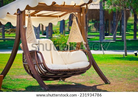 Swinging bench and hammock in the garden - stock photo