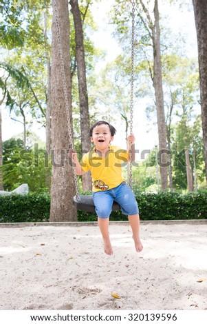Swinging kid. Happy smiling boy flying on a swing. Little child on swing - stock photo