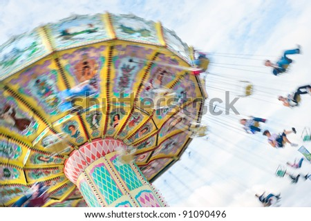 Swinging ride at a carnival with motion blur. - stock photo
