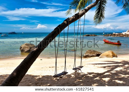 Swings and palm on the sand tropical beach. - stock photo