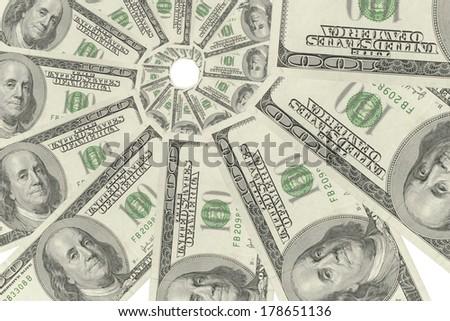 Swirl of hundred-dollar bills on white background. - stock photo