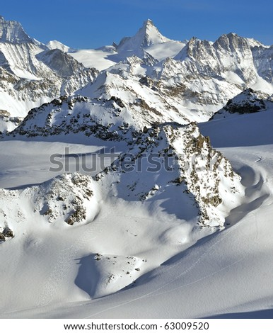 Swiss Alps. Wilderness skiing from helicopters on the rosablanche. The large peak in the background is the Dent d'Herens on the left the matterhorn - stock photo