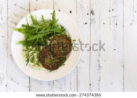 Swiss chard veggie fritters with mash potatoes and rocket leaves on white plate and white rough background, copy splace - stock photo