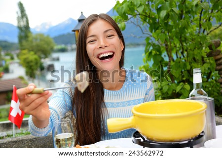 Swiss cheese fondue. Woman laughing showing and eating bread with melted local cheese. Traditional food from Switzerland. People having fun by lake in the Alps on travel in Europe. - stock photo