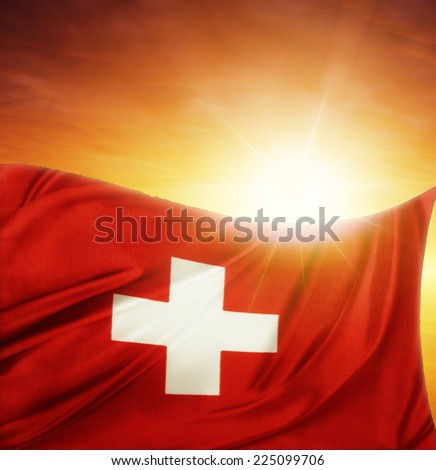 Swiss flag in front of bright sky - stock photo