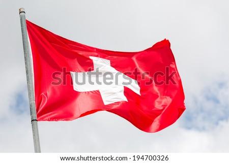 Swiss flag waving on the wind - stock photo