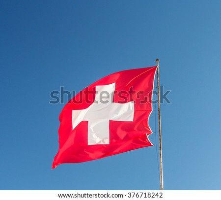 Swiss flag with blue sky - stock photo