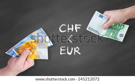 Swiss Franc and Euro banknotes on black board - Euro is stronger than Swiss Franc - stock photo