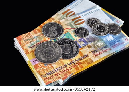 Swiss Franks - a few banknotes and coins of different value isolated on black background - stock photo