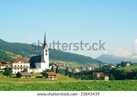 swiss landscape featuring an old church - stock photo