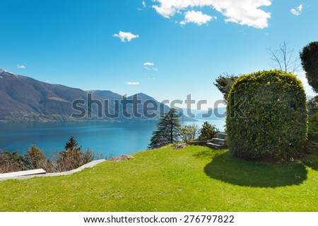 Swiss landscape: garden, mountains and lake - stock photo