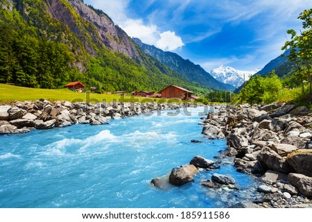 Swiss landscape with river stream and houses - stock photo