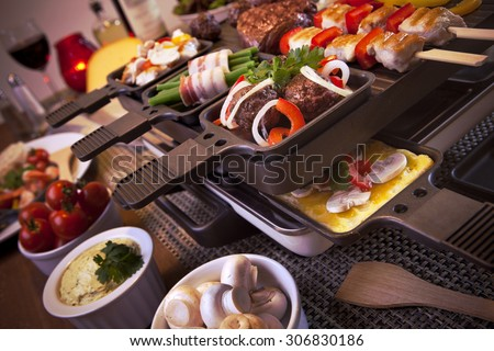Swiss raclette or the Dutch variant 'gourmetten'. A table filled with ingredients for a dish that is usually served on celebratory evenings like Christmas or New Years Eve in The Netherlands. - stock photo