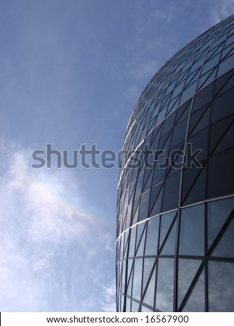 Swiss Re building also know as the Gherkin with bright blue sky London - stock photo