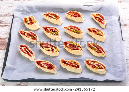 Swiss roll pastry stuffed with ham, olives and sundried tomatoes ready for cooking - stock photo