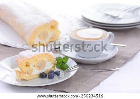 Swiss roll stuffed with banana and cream, a cup of cappuccino in the background - stock photo