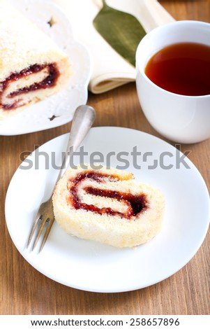 Swiss roll with strawberry jam, sliced and tea