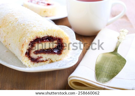 Swiss roll with strawberry jam, sliced and tea - stock photo