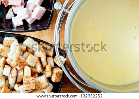 Swiss traditional cheese fondue with ham and croutons. - stock photo