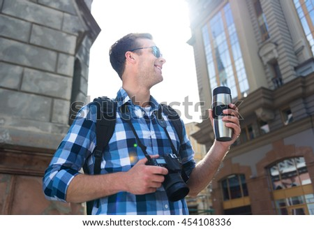 Switch on good mood. Cheerful handsome man drinking coffee and holding photo camera while having a walk - stock photo