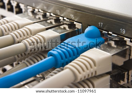 Switch plugged with some RJ45 connectors and copper cables - stock photo