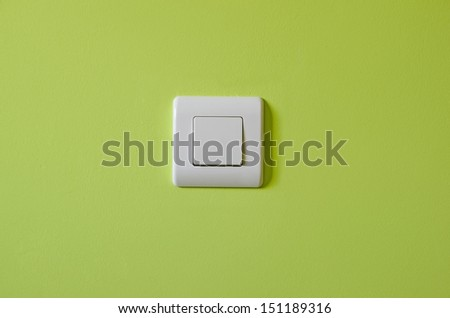 Swith button over a wall painted in green. Electrical element to turn light and electricity on and off - stock photo