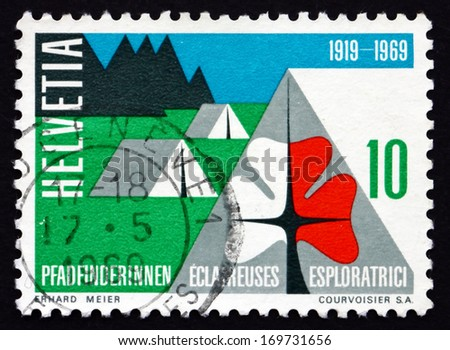 SWITZERLAND - CIRCA 1969: a stamp printed in the Switzerland shows Swiss Girl Scouts' Emblem and Camp, 50th Anniversary of Swiss Girl Scouts, circa 1969 - stock photo