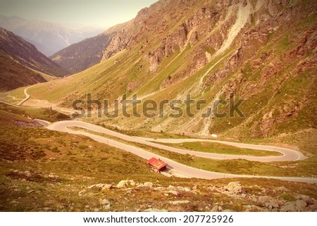 Switzerland. Famous road to Stelvio Pass and Umbrail Pass in Ortler Alps. Alpine landscape. Cross processing color style - retro filtered tone. - stock photo