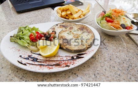 Swordfish steak served on the plate with lemon and vegetables and chips and salad on the side - stock photo