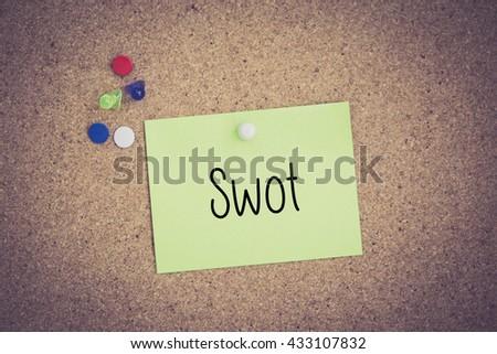 Swot written on sticky note pinned on pinboard - stock photo
