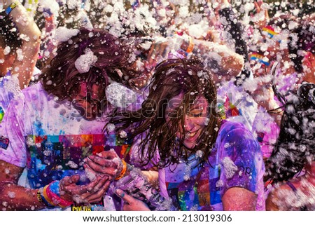 SYDNEY,AUSTRALIA - AUGUST 24,2014: Competitors in the 'Color Run' fun run in Centennial Park. Runners are doused in coloured powder, bubbles and water as they run the 5K course. - stock photo