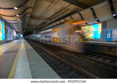 SYDNEY, AUSTRALIA - 31 AUGUST 2013 : The commuter train passes by the platform  in Sydney International Airport train station. Motion blur to denote speed. - stock photo
