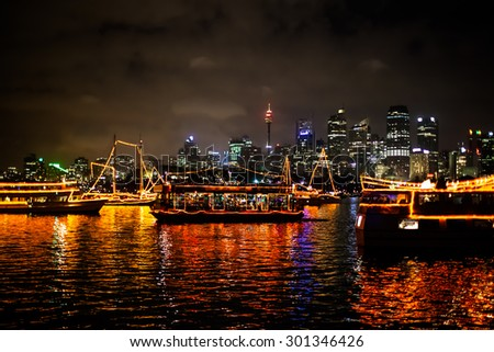 Sydney, Australia - December 31, 2014: Parade of Boats reflecting in Sydney bay in the midnight fireworks of the new years eve 2015, shot from a boat. city skyline in the background.