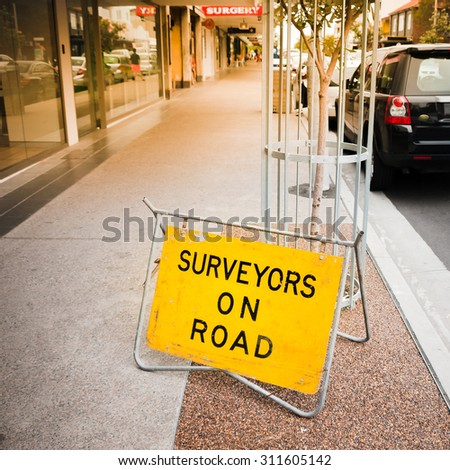 SYDNEY, AUSTRALIA - DECEMBER 10, 2014: Surveyors on road - yellow traffic sign standing on street pavement - stock photo