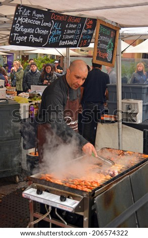 Sydney, Australia - July 19, 2014:  Man Cooking Kebabs on a Barbecue at The Rocks Saturday Morning Market. - stock photo