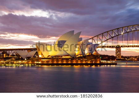 Sydney, Australia - July 11, 2010; Sydney Opera House and the Harbour Bridge at dusk. Taken from Mrs. Macquarie's Point. - stock photo