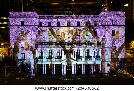 SYDNEY, AUSTRALIA - JUNE 2, 2015;  Customs House is one of the buildings brought to life in projected imagery during Vivid Sydney annual festival event.   Owls and jacaranda on display. - stock photo