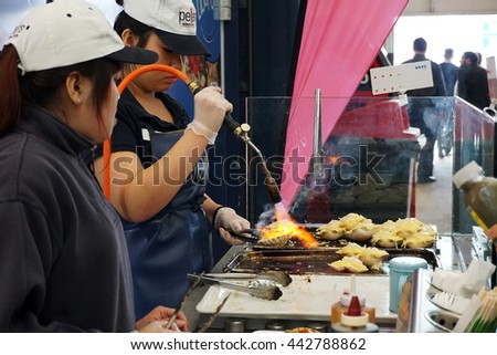 SYDNEY, AUSTRALIA - JUNE 20, 2016: Grilling and burn oysters on flaming fire at Sydney morning market. Freash and Delicious seafood breakfast.