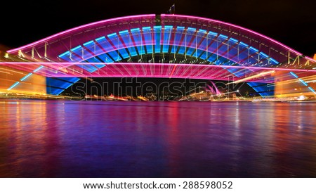 SYDNEY, AUSTRALIA - JUNE 3, 2013;  Sydney Harbour Bridge lit for Vivid Sydney and with a camera zoom effect and spectacular reflections in the harbour water.  Hues of pink and blue - stock photo