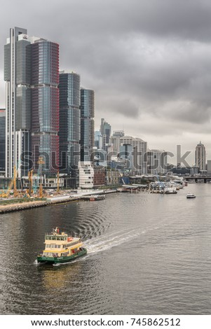 Sydney, Australia - March 21, 2017: HSBC Office towers on shore of Darling Harbour with more towers in back under heavy gray skyline. Ferry approaches on the water. More towers in back.