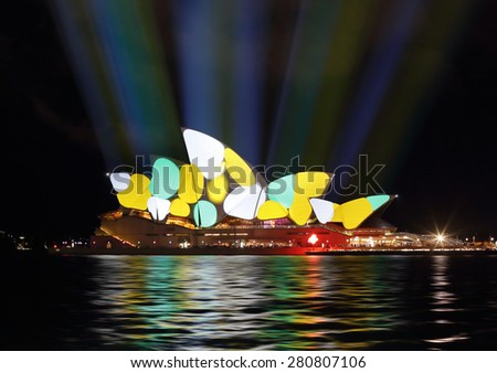 SYDNEY, AUSTRALIA - MAY 22, 2015; Sydney Opera House illuminated with colourful animated imagery of bright yellow and cyan coloured irregular spotty shapes - stock photo