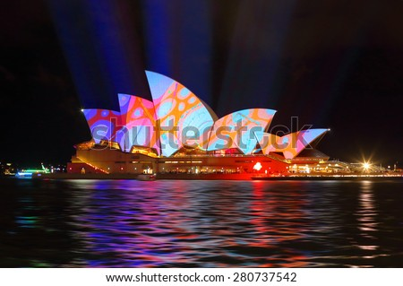 SYDNEY, AUSTRALIA - MAY 22, 2015; Sydney Opera House illuminated with colourful circles design imagery of bright pink, orange and aqua colours during the Vivid Sydney 2015 annual public event. - stock photo