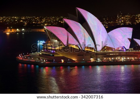 SYDNEY, AUSTRALIA - MAY 23, 2015; Sydney Opera House illuminated with soft pastels of mainly pink and lilac with blue and green abstract design - stock photo