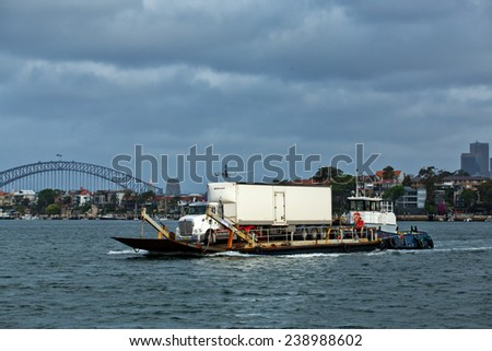 SYDNEY, AUSTRALIA - NOVEMBER 9,2014: A truck is floated across the Harbour on a roll on/roll off barge by a tug. Barges often assist in construction, delivery and installation jobs in the harbour.