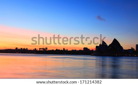 SYDNEY, AUSTRALIA - NOVEMBER 28, 2013;  Sunrise at Sydney, with the Sydney Opera House silhouette and reflections on Sydney Harbour - stock photo