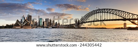 Sydney Australia NSW city landmarks at sunset time when orange sun sets behind harbour bridge in wide panoramic view - stock photo