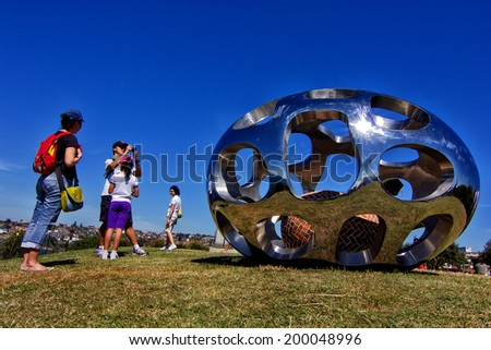 SYDNEY,AUSTRALIA - OCTOBER 20,2012: People inspect exhibits in the annual 'Sculpture by the sea' exhibition. SBTS is the world's largest free sculpture exhibition. - stock photo