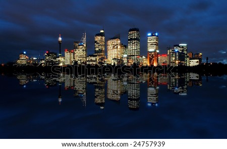 sydney cbd panorama at night, buildings reflection in water, dark cloudy night sky - stock photo