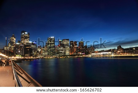 SYDNEY, CIRCULAR QUAY, AUSTRALIA - NOVEMBER 27, 2013; Nightscape scene of cityscape buildings aglow against a twilight sky and harbor reflections.